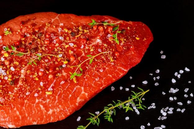 Carne de lombo cru com ervas, sal e pimenta sobre placa de pedra preta.