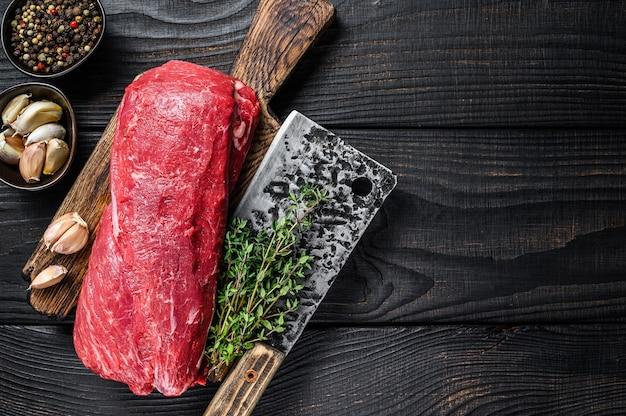 Carne de lombo crua para filé mignon de bifes em uma tábua de madeira com cutelo de açougueiro. fundo de madeira preto. vista do topo. copie o espaço.