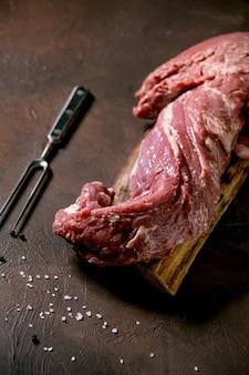 Carne de lombo de carne crua inteira fresca na placa de madeira com garfo de carne de metal, sal e pimenta sobre fundo de textura marrom escuro. conceito de fundo de cozimento de alimentos. fechar-se