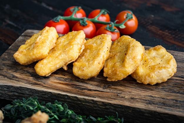 Carne de nuggets de frango frito crocante na velha mesa de madeira escura.