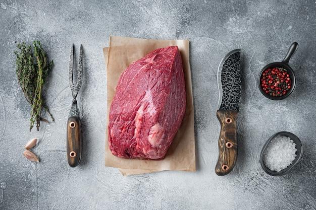 Carne de peito bovina crua definida com faca de cutelo de açougueiro velho, mesa cinza, vista de cima plana