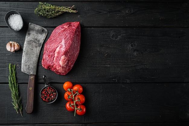 Carne de peito bovina crua definida com faca de cutelo de açougueiro velho, mesa de madeira preta, vista de cima plana