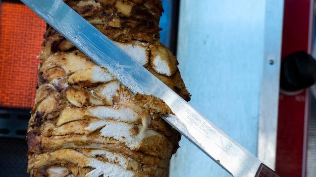 Carne de peito de frango. o doador é cortado do espeto de centrifugação.