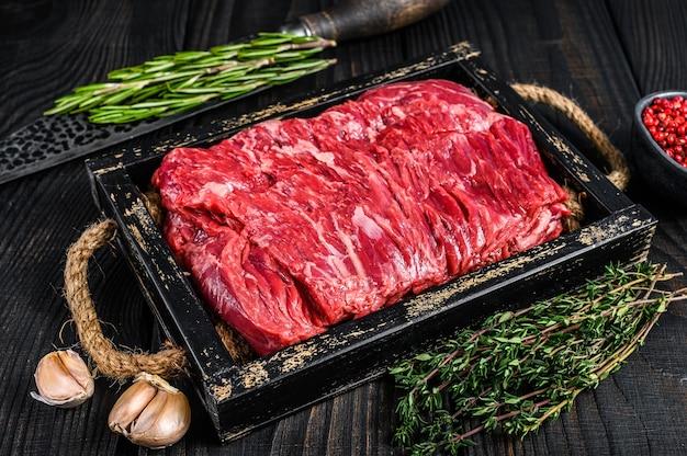 Carne de peito de vaca crua fresca cortada com ervas em uma bandeja de madeira