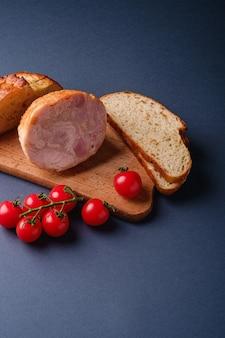 Carne de peru, ramo de tomate cereja fresco e pão fatiado de pão na tábua de madeira