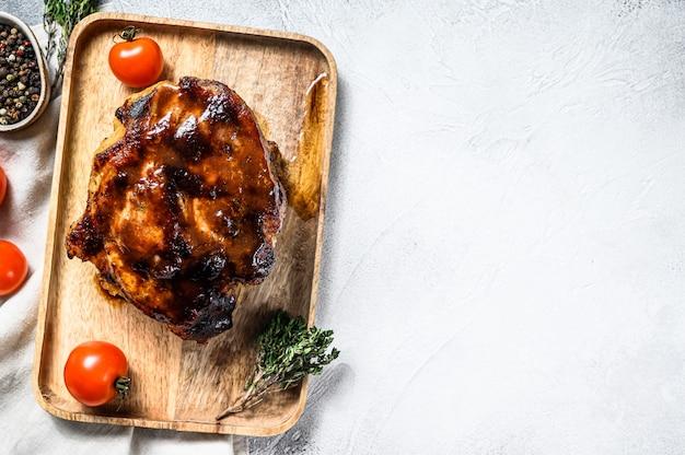 Carne de pescoço de porco assado com especiarias na tábua. espaço cinza. vista do topo. copie o espaço