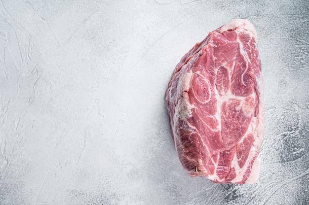Carne de pescoço de porco crua para bife de costeleta na mesa de cozinha. fundo branco. vista do topo. copie o espaço.