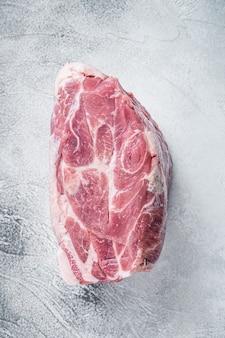 Carne de pescoço de porco crua para bife de costeleta na mesa de cozinha. fundo branco. vista do topo.