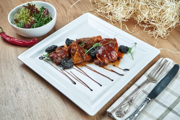Carne de porco apetitosa cozida em molho agridoce e ameixas secas em um prato branco. feche acima da vista. comida saborosa para o almoço