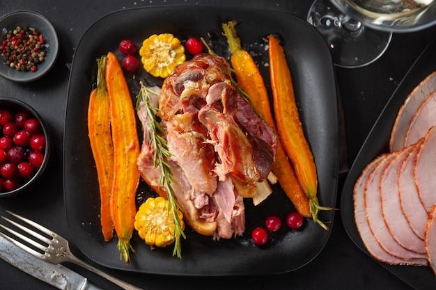 Carne de porco assada de natal com legumes e especiarias no prato. fechar-se