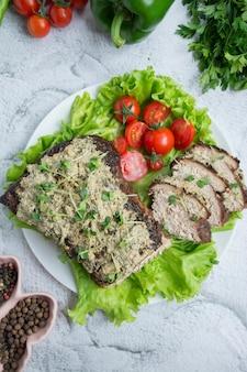 Carne de porco assada, picada em um molho de nozes e hortelã em um prato branco com ervas e legumes frescos. mesa de luz.