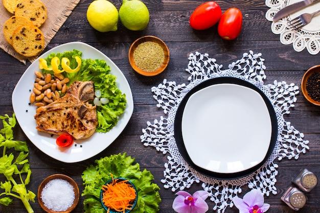Carne de porco bife caseiro com especiarias folhas de alface na tábua de madeira e um prato