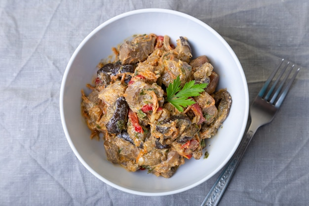 Carne de porco com berinjela, tomate, pimentão e cenoura em um molho cremoso. fechar-se.