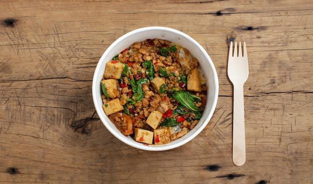 Carne de porco com manjericão tailandês frito com arroz em uma caixa de papel para comida
