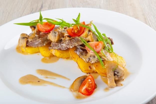 Carne de porco cozida com cogumelos tomate batatas com molho de mostarda
