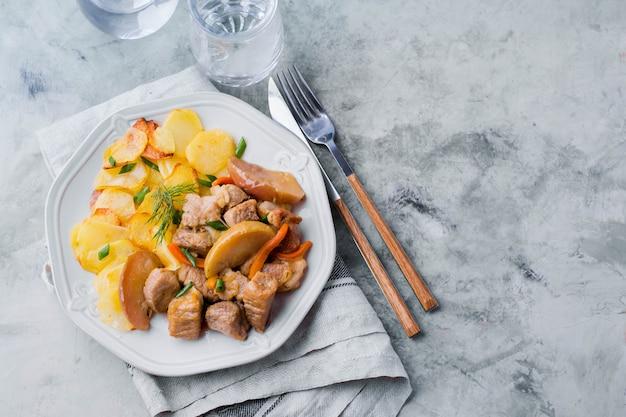 Carne de porco cozida com maçãs com batatas para enfeitar no prato na mesa cinza