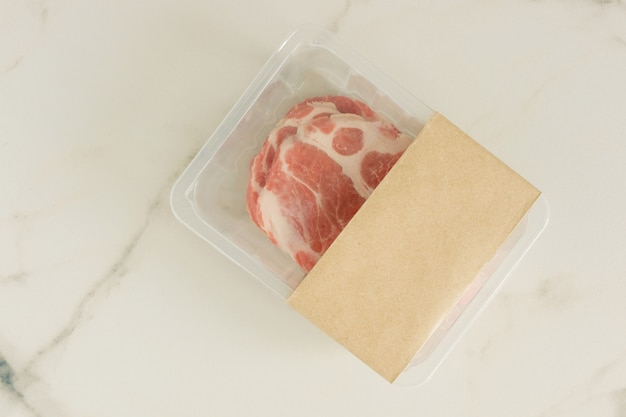 Carne de porco crua bife a vácuo embalado em fundo de mármore, vista superior, maquete para designers.