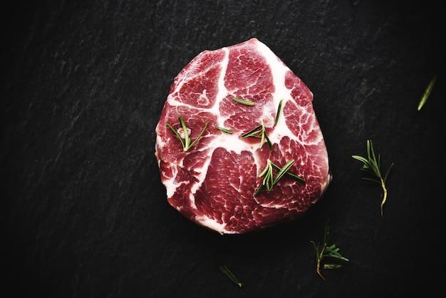 Carne de porco crua - bife fresco pronto para grelhar com alecrim especiarias em preto