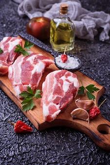 Carne de porco crua e ingredientes para cozinhar. foco seletivo