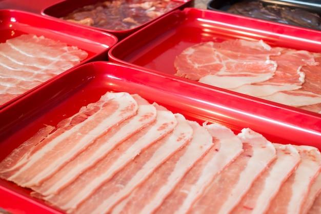Carne de porco crua em fatias, preparando-se para sukiyaki caseiro