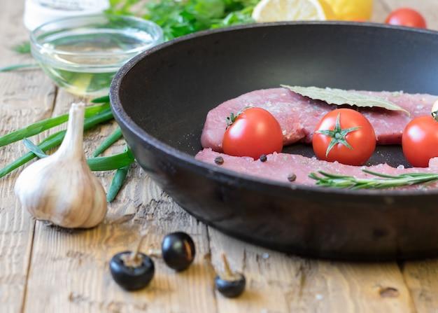 Carne de porco crua em uma frigideira sobre uma mesa rústica.