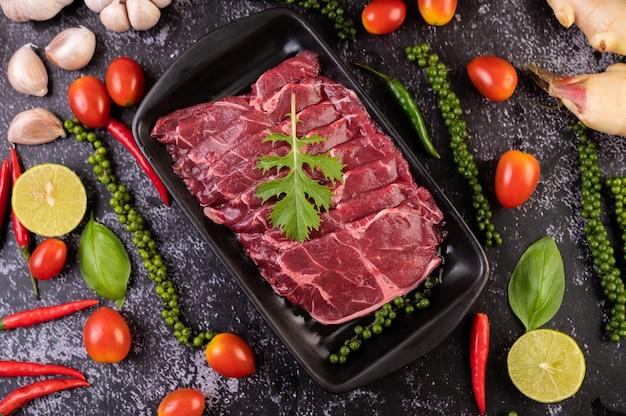 Carne de porco crua fatiada usada para cozinhar com sementes de pimentão, tomate, manjericão e pimenta fresca.