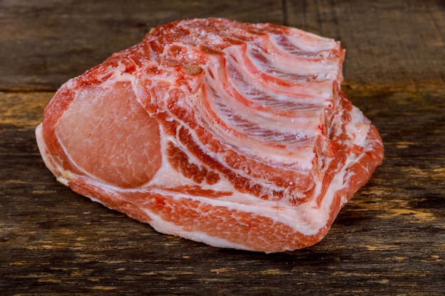 Carne de porco crua na mesa de madeira.