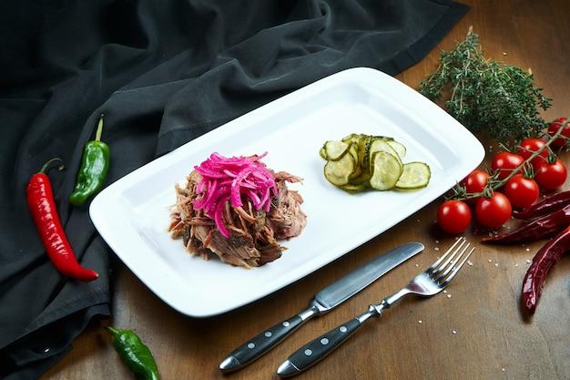 Carne de porco desfiada é um prato de churrasco clássico. carne de porco assada suculenta rasgada em fibra com cebolas em conserva em um prato branco. feche acima da vista. foco seletivo. comida para o almoço
