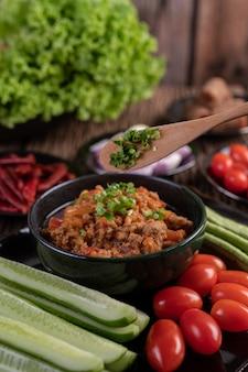 Carne de porco doce em uma tigela preta, completa com pepinos, feijões longos, tomates e acompanhamentos