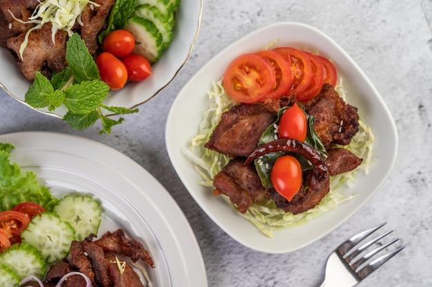 Carne de porco frita coberta com gergelim, colocado em um prato branco.