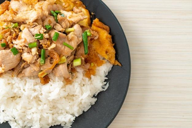 Carne de porco frita com alho e ovo coberto com arroz - comida asiática
