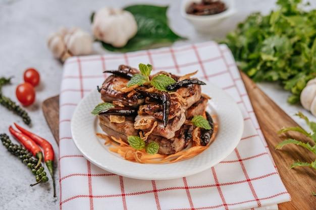 Carne de porco frita com chili frito cebola frita e hortelã em um prato branco.