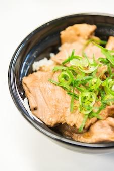 Carne de porco frita com molho doce em cima da tigela de arroz