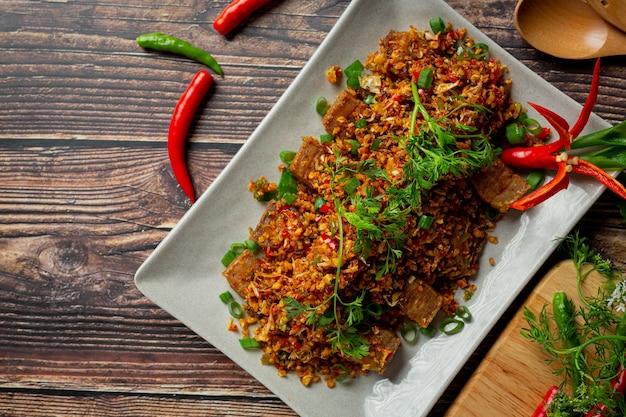 Carne de porco frita com pimenta seca e sal em fundo escuro