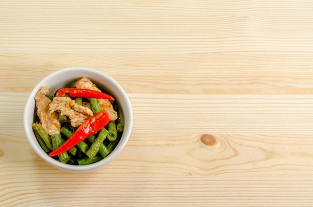 Carne de porco frita picante stir com pasta de curry vermelho e yard feijão longo, menu de comida tailandesa