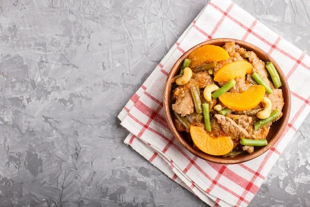 Carne de porco fritada com pêssegos, caju e feijões verdes em uma bacia de madeira em um fundo concreto cinzento, espaço da cópia.
