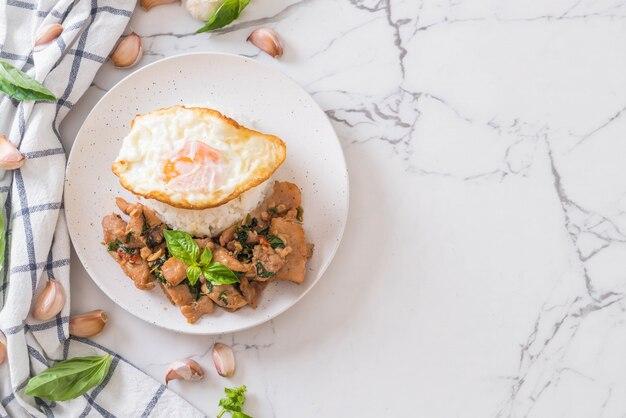 Carne de porco frito com manjericão no arroz e ovo frito
