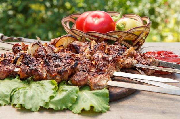 Carne de porco grelhada em espetos de metal assados na grelha e folhas de alface na tábua de cortar de madeira com molho de tomate em uma tigela e pepino e pimentão em uma cesta de vime. churrasco, piquenique