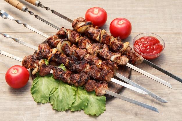 Carne de porco grelhada em espetos de metal assados na grelha e folhas de alface na tábua de madeira com molho de tomate em uma tigela e tomates frescos. churrasco, vista superior