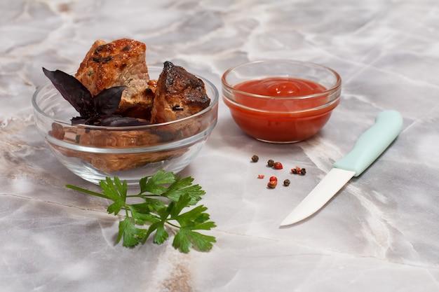 Carne de porco grelhada em uma tigela com molho e verduras.