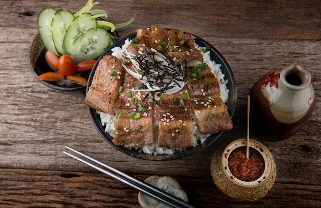 Carne de porco grelhada fatia com chama de carvão vegetal definido na tigela de arroz em estilo japonês.