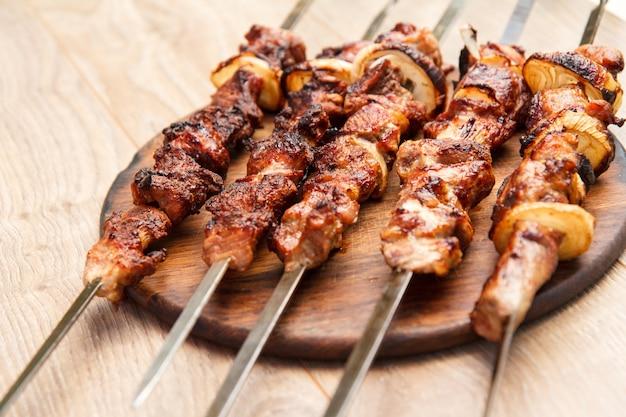 Carne de porco grelhada no espeto assado na grelha na tábua de madeira. churrasco, piquenique