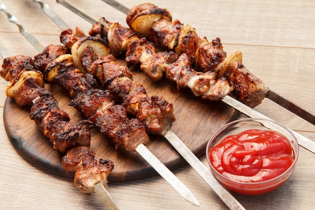 Carne de porco grelhada no espeto assado na grelha na tábua de madeira com molho de tomate em uma tigela. churrasco, piquenique