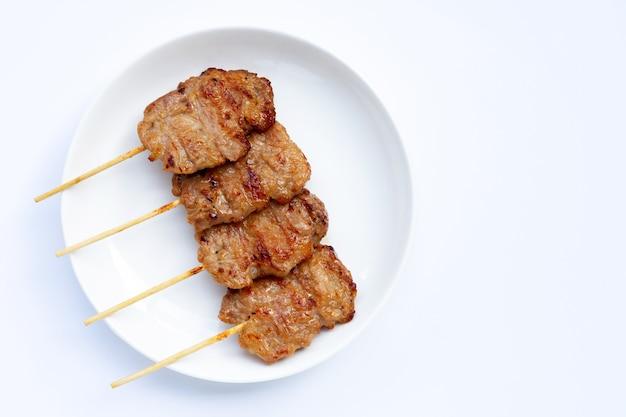 Carne de porco grelhada no fundo branco.