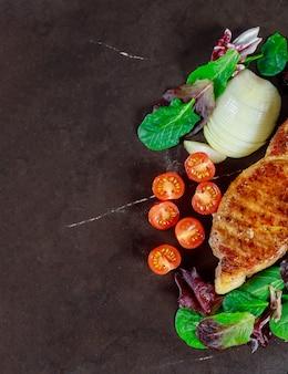 Carne de porco grelhada rara média do bife suculento com especiarias e egetables.