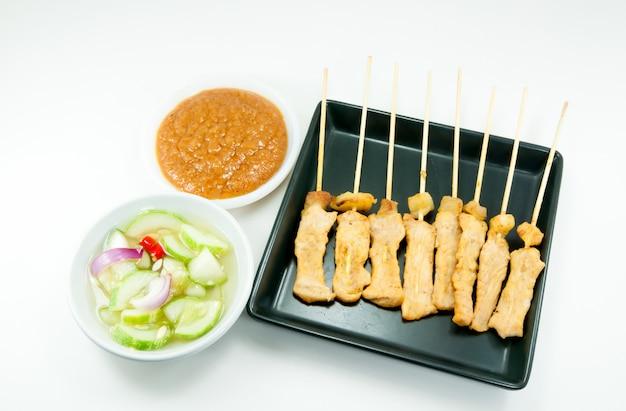 Carne de porco grelhada satay com molho de amendoim e vinagre no fundo branco