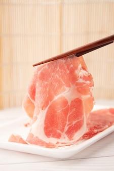 Carne de porco magra em fatias finas, carne de porco shabu-shabu, os pauzinhos estão pegando as fatias de porco.
