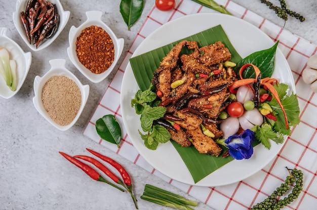 Carne de porco nam tok com pimenta frita, tomate, limão, pepino e pimenta fresca. comida tailandesa.