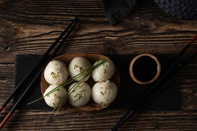 Carne de porco no vapor e dim sum de camarão em pedra de ardósia em mesa de madeira em restaurante asiático