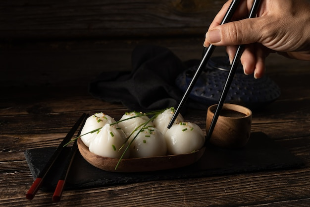Carne de porco no vapor e dim sum de camarão na pedra de ardósia na mesa de madeira
